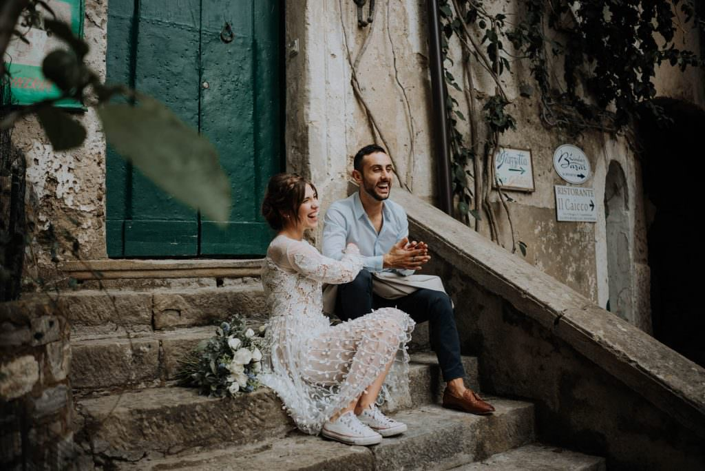 Bridal couple on steps in Castellebate in Italy